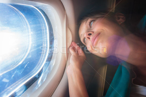 Happy, female airplane passanger enjoying the view from the cabo Stock photo © lightpoet