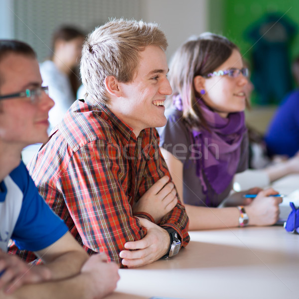 Handsome college student sitting in a classroom full of students Stock photo © lightpoet