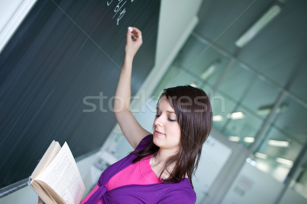 pretty young college student writing on the chalkboard/blackboar Stock photo © lightpoet