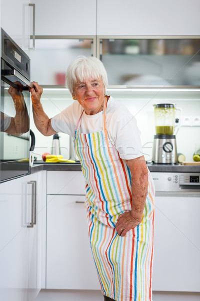 Senior woman cooking in the kitchen - eating and cooking healthy Stock photo © lightpoet