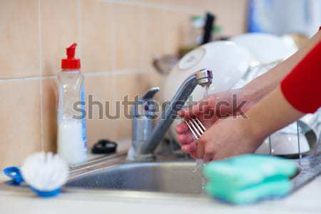 woman hands rinsing dishes under running water in the sink Stock photo © lightpoet