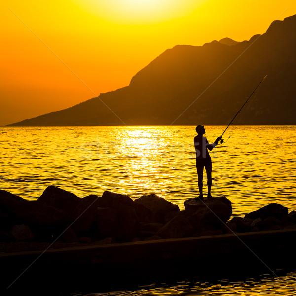 Silhueta praia colorido pôr do sol pescador céu Foto stock © lightpoet