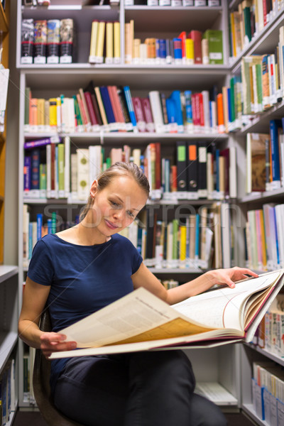 Pretty, young woman studying an old book in archives Stock photo © lightpoet