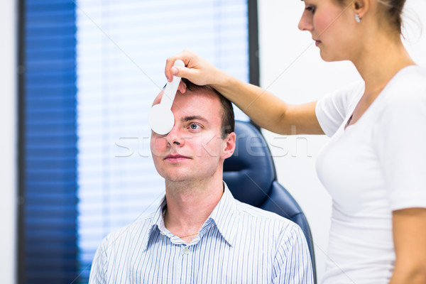 Hhandsome young man having his eyes examined by an eye doctor Stock photo © lightpoet