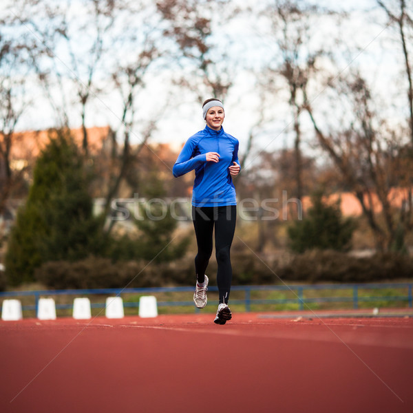 Young woman running at a track and field stadium Stock photo © lightpoet