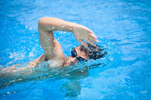 Young man swimming the front crawl in a pool Stock photo © lightpoet