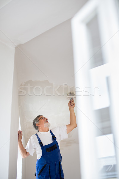 Painter man at work with a paint bucket, wall painting concept Stock photo © lightpoet