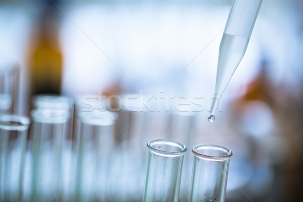 Liquid drop from laboratory glass pipette to test tube Stock photo © lightpoet