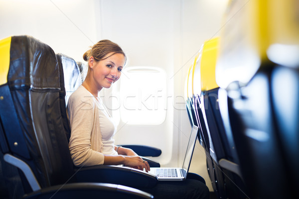 Stock photo: Young woman on board of anairplane