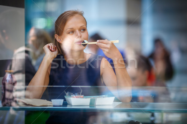 Pretty, young woman eating sushi in a restaurant Stock photo © lightpoet