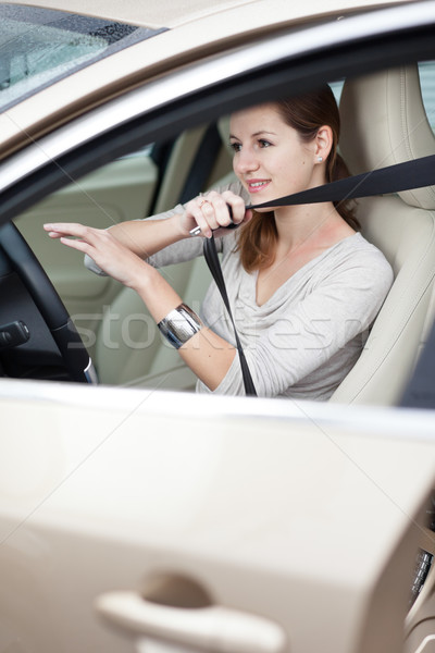 Stock photo: Pretty young woman driving her new car