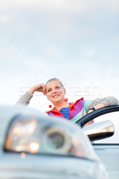Portrait of a cheerful female teen driver, by her new car Stock photo © lightpoet