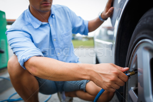 Driver checking air pressure and filling air in the tires of his Stock photo © lightpoet