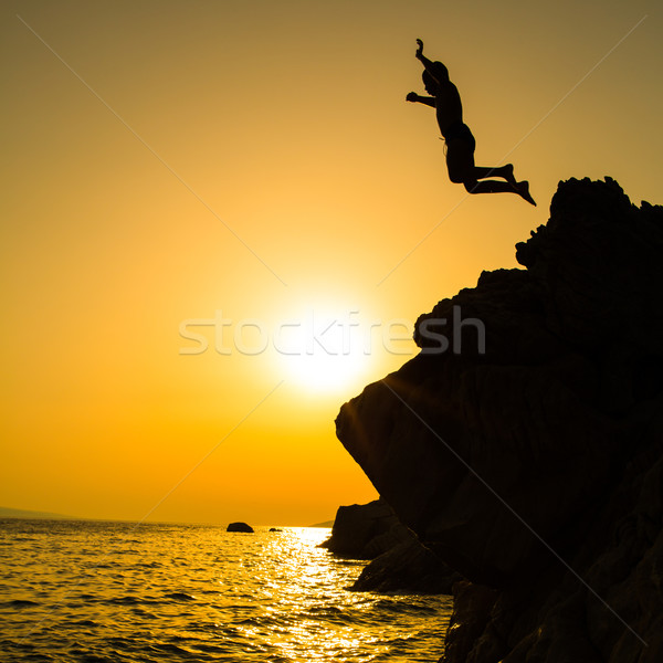 Boy jumping to the sea. Silhouette shot against the sunset sky.  Stock photo © lightpoet
