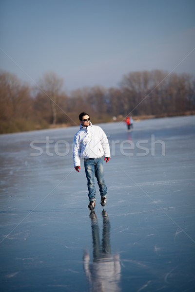Handsome young man ice skating outdoors on a pond Stock photo © lightpoet