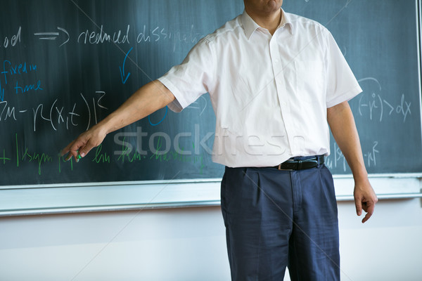 teacher teaching mathematics while pointing at blackboard Stock photo © lightpoet