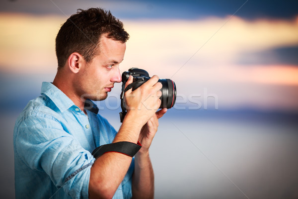 Handsome young photographer using his modern DSLR outdoors Stock photo © lightpoet