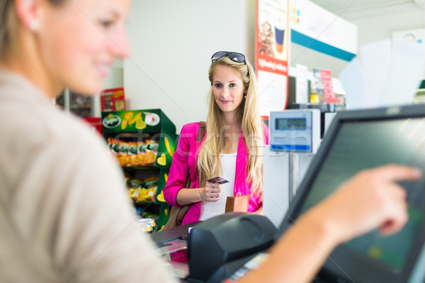 Mooie jonge vrouw betalen counter kruidenier Stockfoto © lightpoet