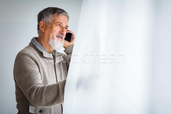 Handsome senior man calling on his cell phone  Stock photo © lightpoet