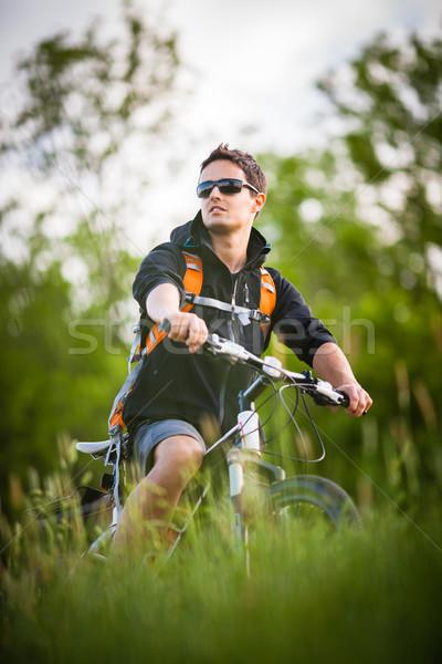 Jóképű fiatalember motorozás vidék tavasz fitnessz Stock fotó © lightpoet