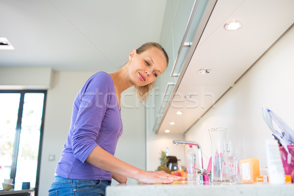Pretty, young woman cleaning her modern kitchen  Stock photo © lightpoet