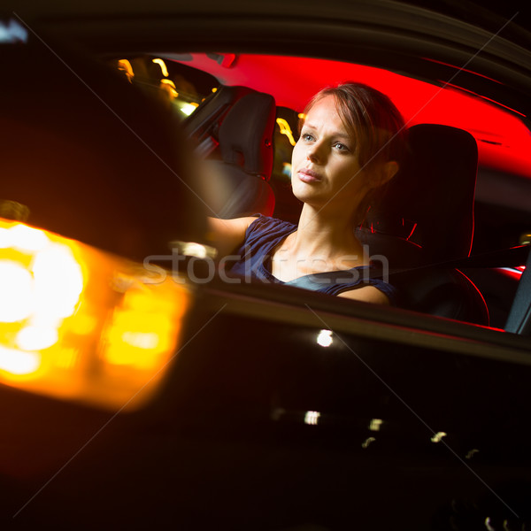 Pretty, young woman driving her modern car at night, in a city Stock photo © lightpoet