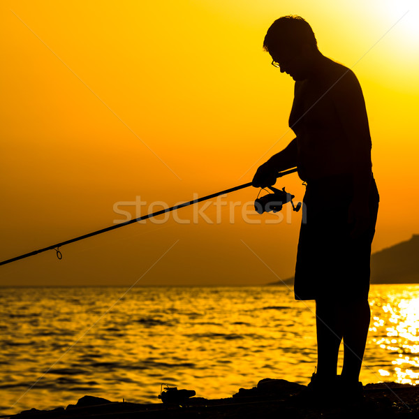 Fisherman's silhouette on the beach at colorful sunset Stock photo © lightpoet