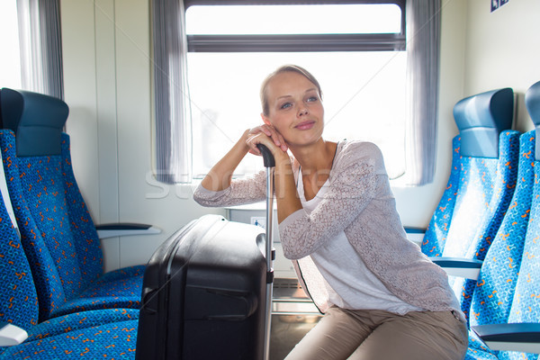 Pretty young woman traveling on a train with her big trunk Stock photo © lightpoet