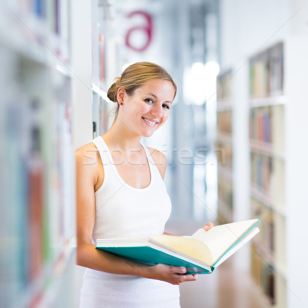 Stock photo: pretty young college student in a library