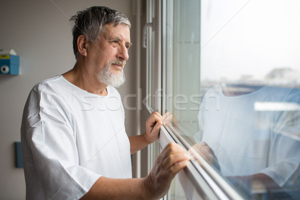 Patient at a hospital, looking from a window in his room Stock photo © lightpoet