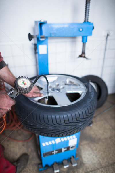Auto mechanic in a garage checking the air pressure in a tyre Stock photo © lightpoet