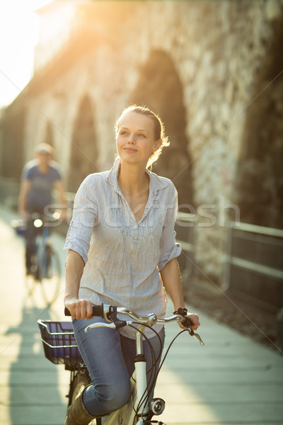 Stock photo: Pretty, young woman riding a bicycle in a city with her boyfrien