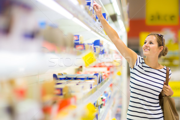 Beautiful young woman shopping for diary products at a grocery Stock photo © lightpoet