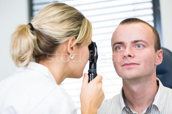 Optometry concept - handsome young man having her eyes examined  Stock photo © lightpoet