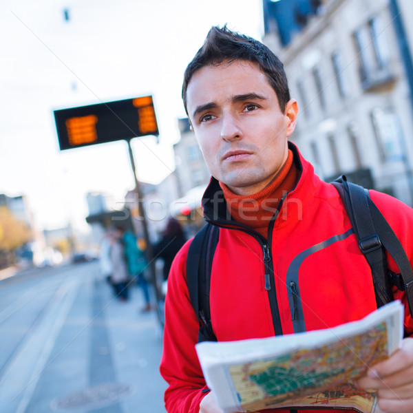 Just arrived: handsome young man studying a map on a bus stop Stock photo © lightpoet