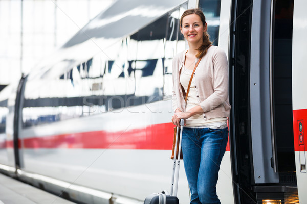 Stock photo: Pretty young woman boarding a train (color toned image)