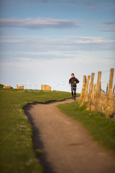 Young woman on her evening jog along the seacoast Stock photo © lightpoet