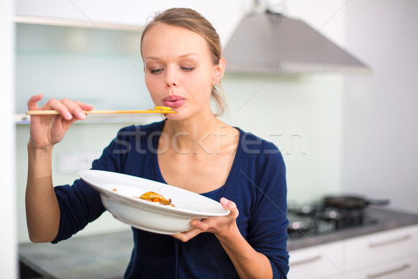 Pretty, young woman cooking a diner in a modern kitchen Stock photo © lightpoet