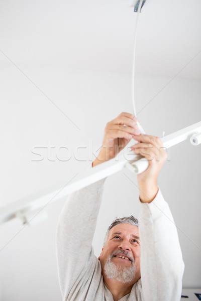 Senior man installing a ceiling light in a  renovated appartment Stock photo © lightpoet