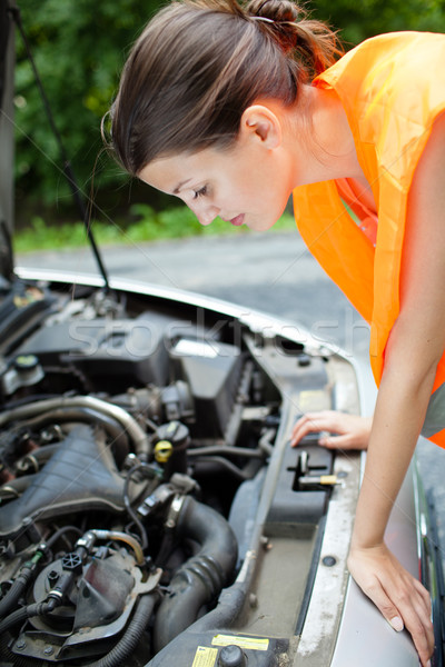 Young female driver bending over  the engine of her broken down car Stock photo © lightpoet