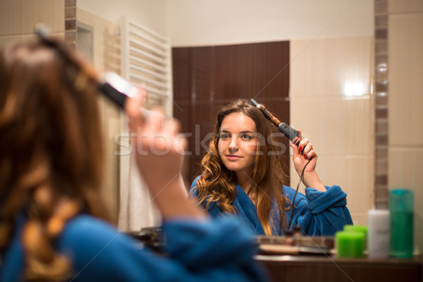 Pretty, young woman curling her hair in front of her bathroom mi Stock photo © lightpoet