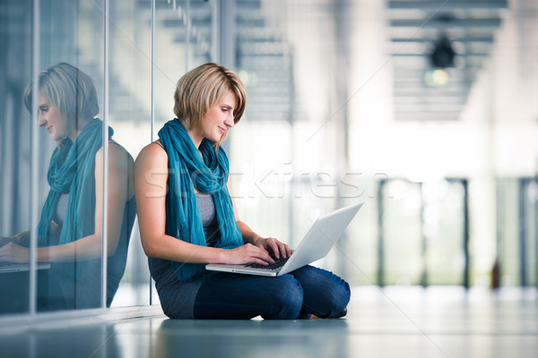 Pretty female student with a laptop computer on university campus Stock photo © lightpoet