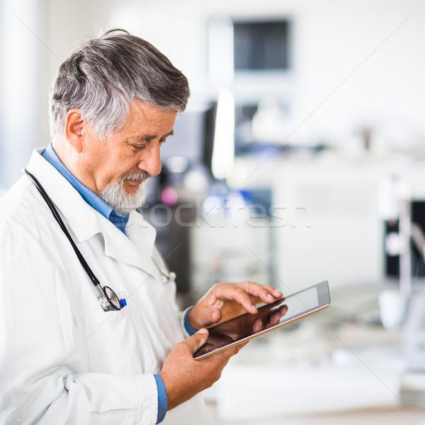 Senior doctor using his tablet computer at work  Stock photo © lightpoet