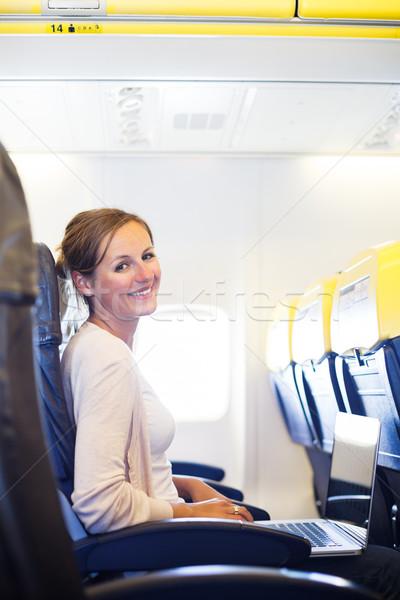 Fiatal nő tábla dolgozik laptop számítógép repülőgép számítógép Stock fotó © lightpoet