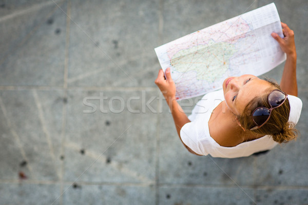 Pretty young female tourist studying a map Stock photo © lightpoet