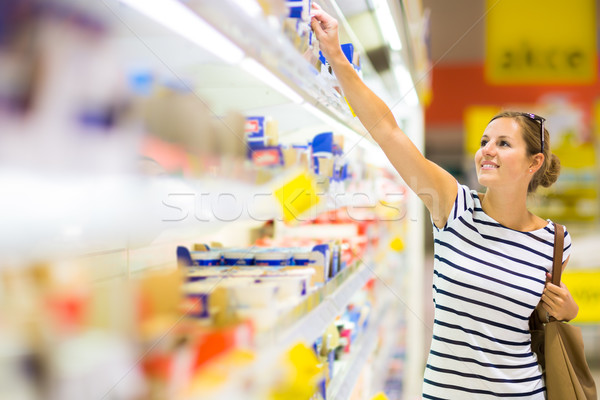 Stock photo: Beautiful young woman shopping for diary products at a grocery s