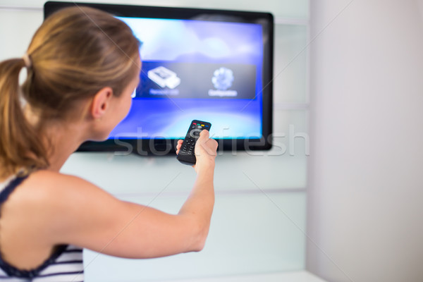 Young woman at home watching TV, turning it on, changing channel Stock photo © lightpoet