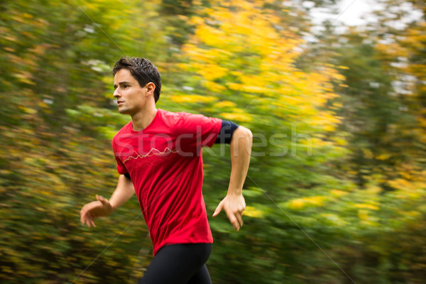Young man running outdoors in a city park on a fall/autumn day Stock photo © lightpoet