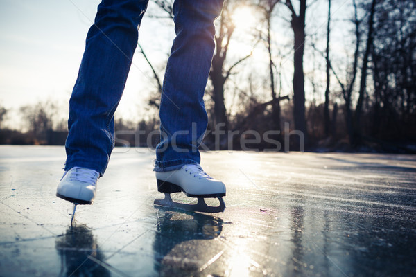 Stock photo: Young woman ice skating outdoors on a pond