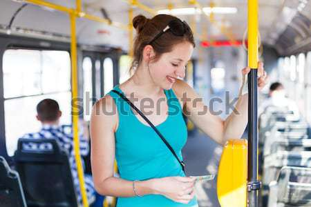 Stock photo: Pretty, young woman on a streetcar/tramway, during her commute t